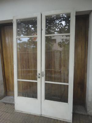 Puertas grandes doble de madera maciza con vidrio repartido.