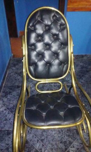 Sillon Mecedora de Bronce con tapizado de cuero negro.
