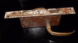 Antigua cerradura, dos picaportes de bronce y la llave.