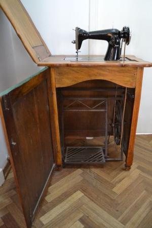 Máquina de coser antigua con pie de hierro y mueble externo