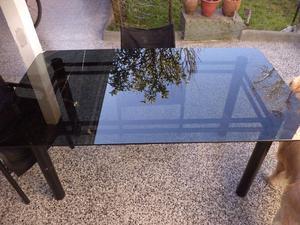 mesa de vidrio con estructura de metal negro con vidrio fume