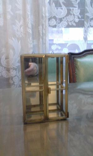 Hermosa vitrinita de vidrio y bronce, fondo espejado