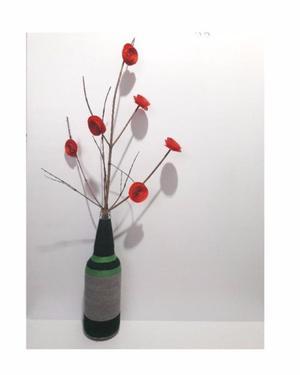 Botella decorada con hilo y rama con flores de cartulina