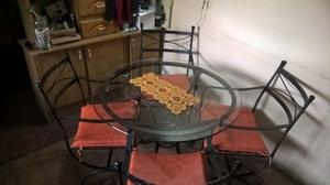 mesa redonda de vidrio con sillas