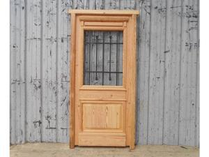 Puerta de frente en madera antigua de pinotea con reja