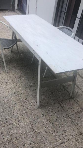 Mesa de madera y sillas de mimbre de jardín
