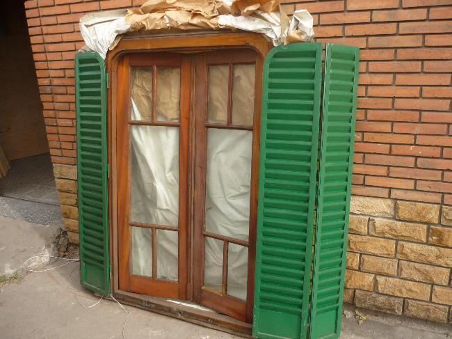 ventana madera con postigon de hierro
